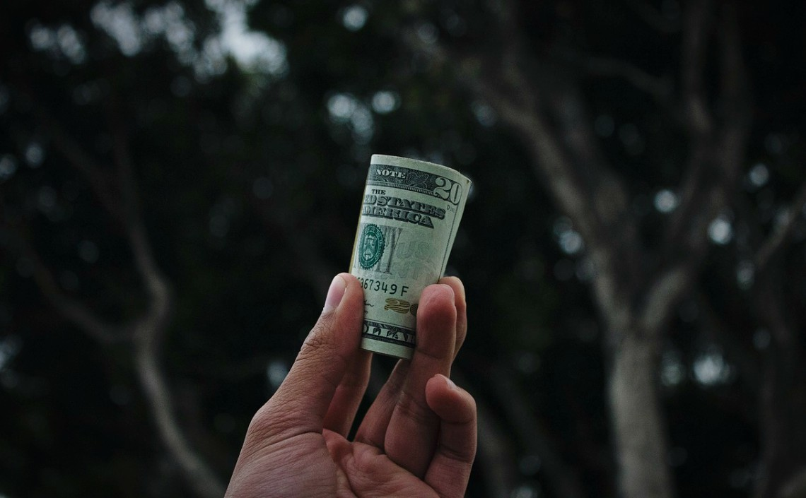 A man's hand holding a roll of $20 bills, against a dark background