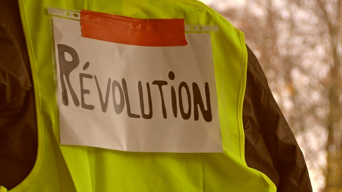 A yellow vest with a sign saying Revolution taped on it.
