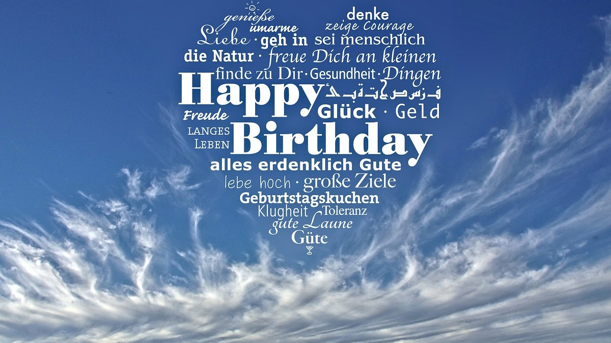 Happy Birthday written in the sky, in many different languages, in the shape of a heart, against a brilliant blue sky, nestled in beautiful white clouds.