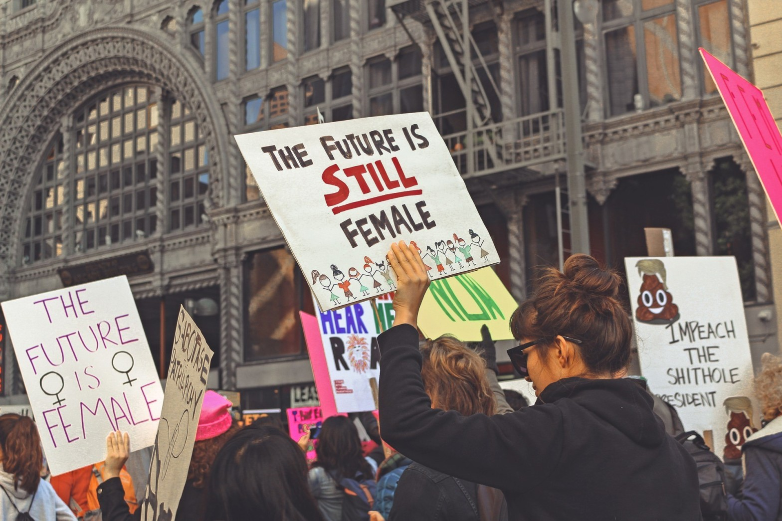 """Woman marcher holding sign that says """"The future is STILL female."""""""